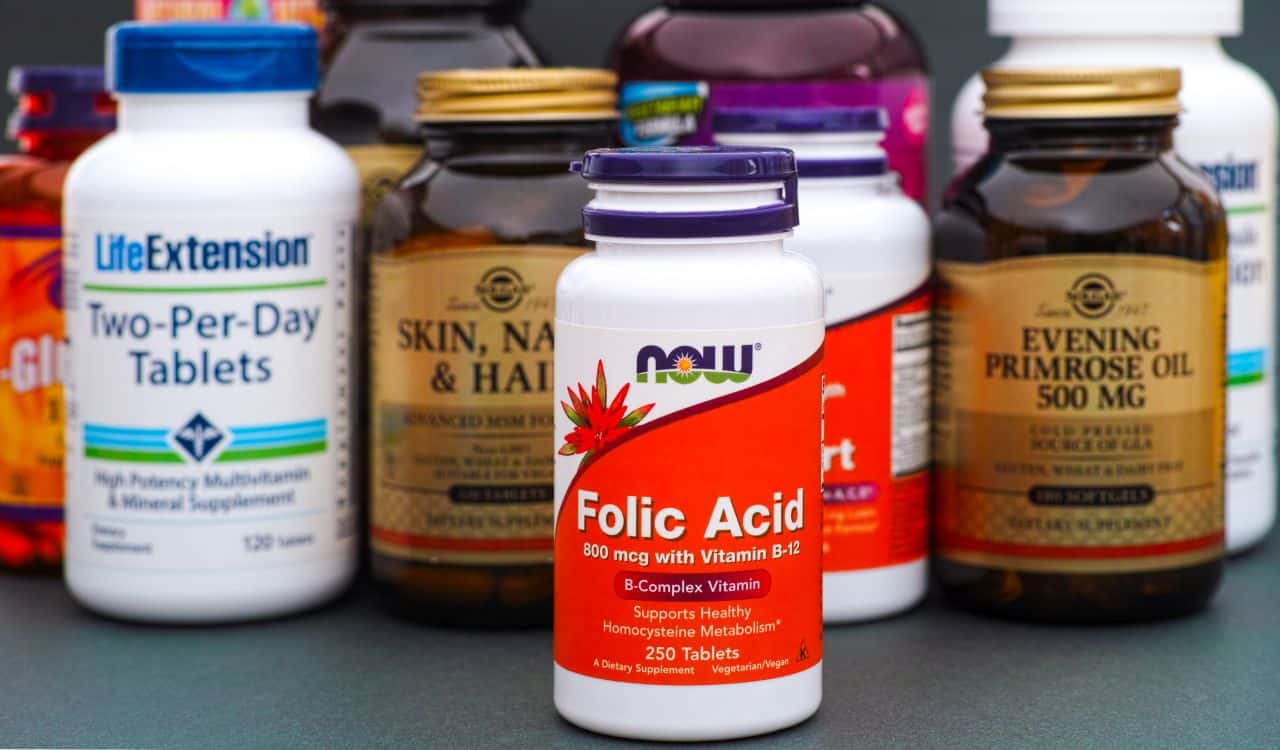 Bottle with Folic Acid by NOW with vitamins and dietary supplement behind it