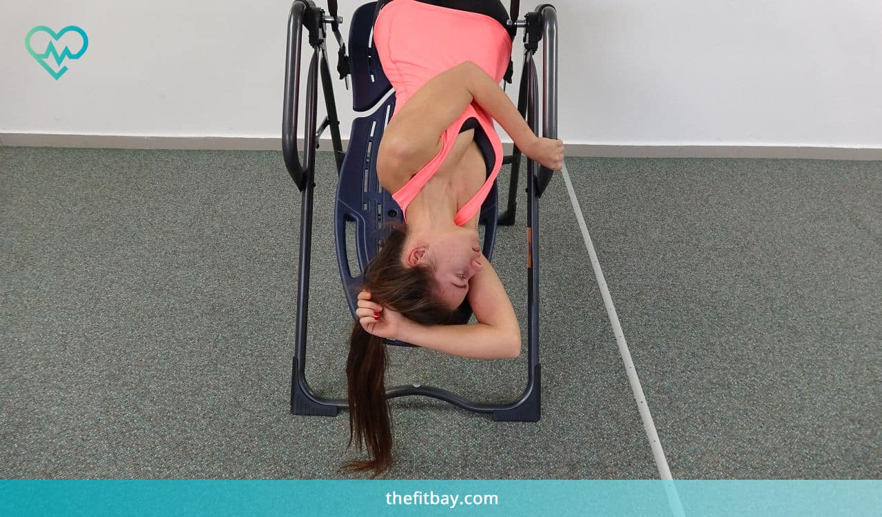 Woman Exercises on Inversion Table - Trunk Rotation