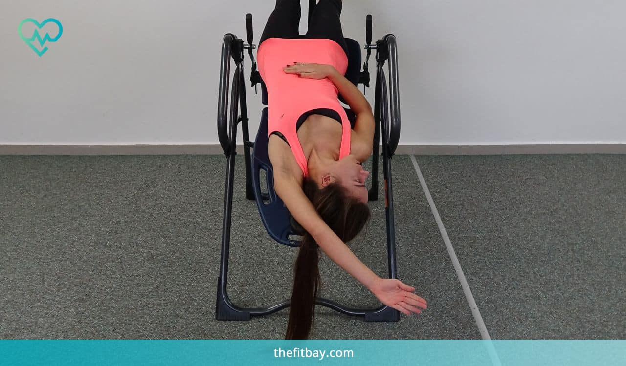 Woman Exercises on Inversion Table - Overhead Stretch