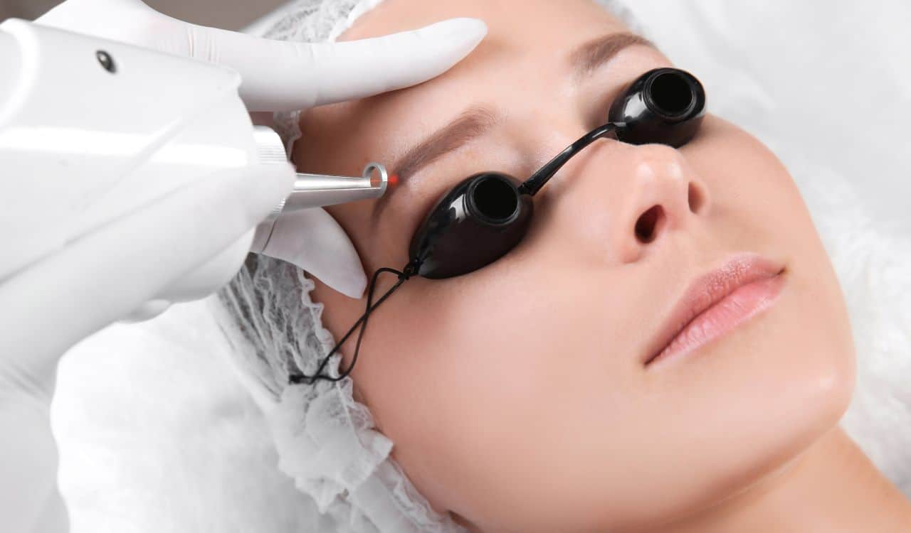 Young Woman Undergoing Laser Removal Of Eyebrow
